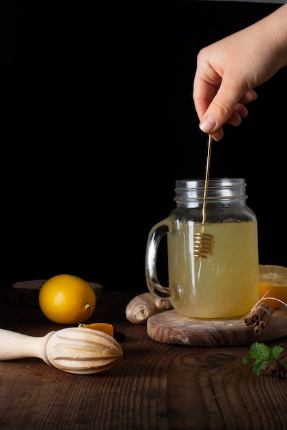 Close-up hand mixing jar filled with homemade lemonade Free Photo