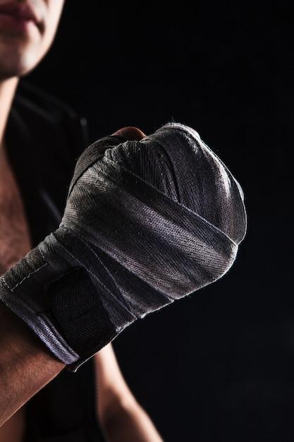 Mano del primo piano dell'uomo muscolare con la fasciatura Foto Gratuite