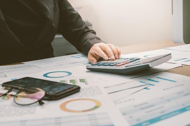 Закройте руку бизнесмен бухгалтер или банкир с помощью калькулятора Premium Фотографии