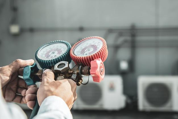 Крупным планом рука инженера, использующего измерительный коллектор для заполнения промышленного заводского кондиционера. Premium Фотографии