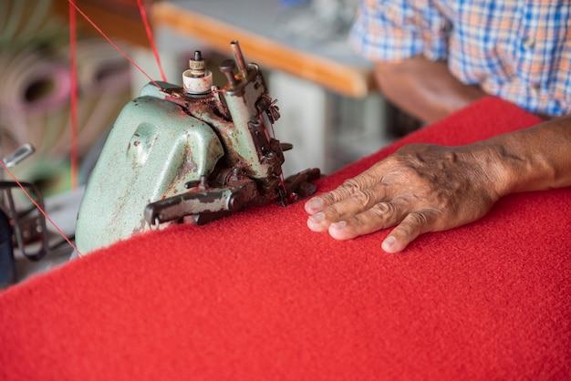 赤い敷物を縫う老人の手をクローズアップ Premium写真