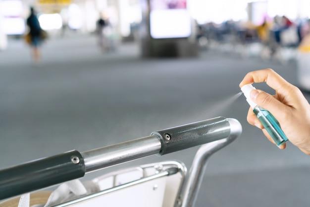 Закройте вверх руку женщины, дезинфицируя троллейбус аэропорта, распыляя алкоголь из бутылки, защита от инфекционных вирусов, бактерий и микробов. концепция здравоохранения. Premium Фотографии