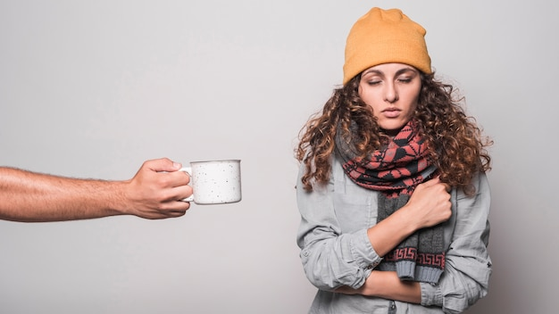 Close-up of hand offering coffee to sick woman having cold and flu Free Photo