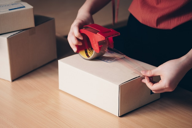 Close up hand packing parcel boxes prepare to delivery Premium Photo