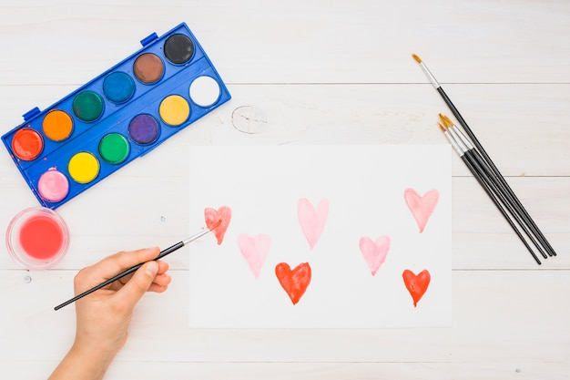 Close-up of hand painting heart shapes with water color on white sheet Free Photo