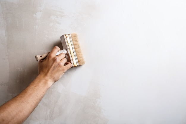 Close up of hand painting wall with brush. Free Photo