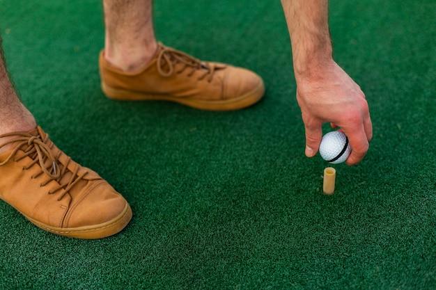 Close-up hand placing golf ball Free Photo
