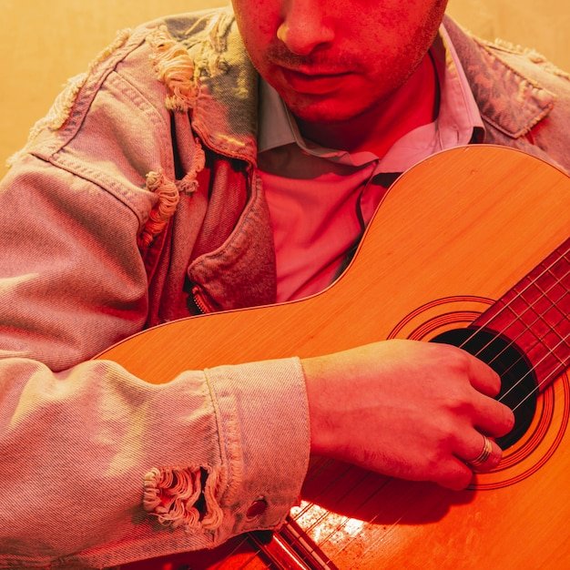 Close-up hand playing acoustic guitar Free Photo