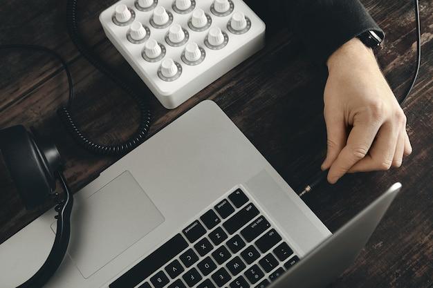 Крупным планом рука вставляет шнур наушников в музыкальный порт стереоразъема в ноутбуке retina Бесплатные Фотографии