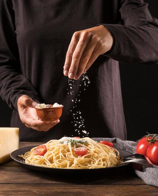 Крупным планом руки наливают сыр на макароны Premium Фотографии