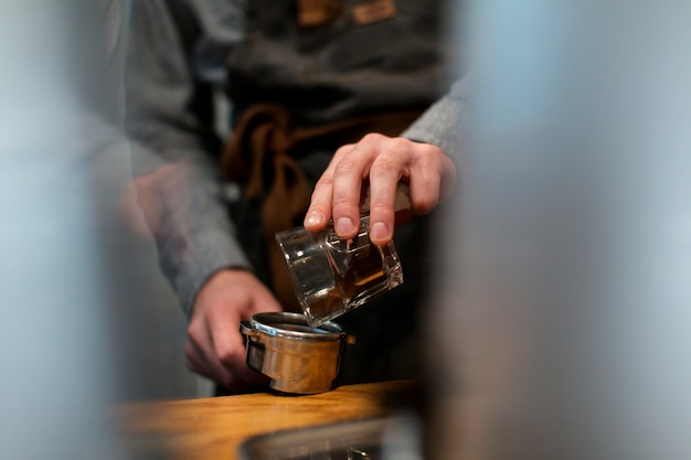 Close-up of hand pouring coffee in pot Free Photo