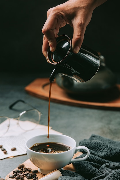 A close-up of a hand pouring coffee water into a coffee cup, international coffee day concept Free Photo