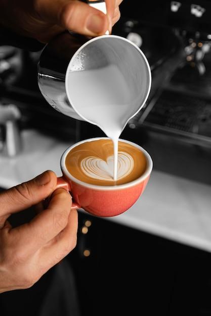클로즈업 손 커피에 우유를 붓는 무료 사진