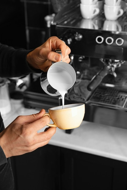 カップに牛乳を注ぐクローズアップ手 無料写真