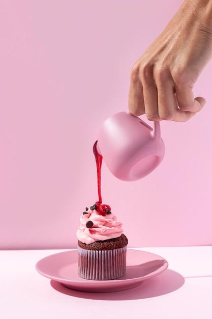 Крупным планом рука наливает сироп на кекс Premium Фотографии