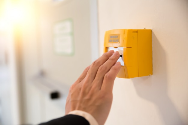 Close-up hand press emergency switch and exit the door. Premium Photo