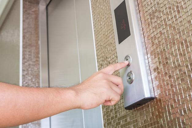 Close up hand pressing silver elevator button Premium Photo