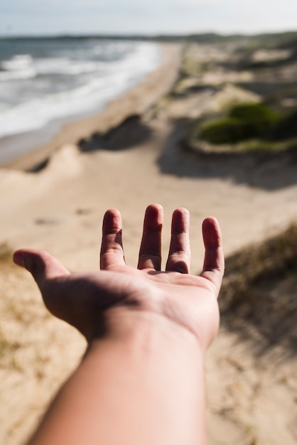 Close-up hand reaching at beach landscape Free Photo