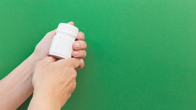 Close-up of hand's holding pill plastic bottle against green background Free Photo