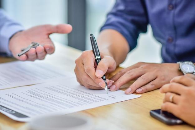 Крупным планом стороны подписать контракт на покупку дома Premium Фотографии