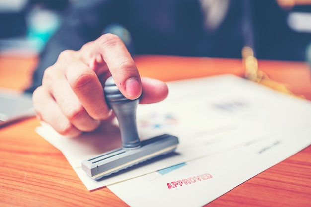 Close-up hand stamping of businessman for signing approval on documents , business concept Premium Photo