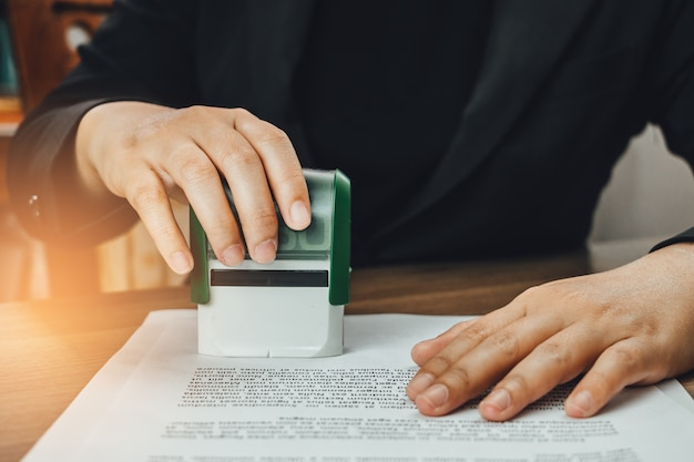 Close-up hand stamping of businesswoman for signing approval on documents Premium Photo