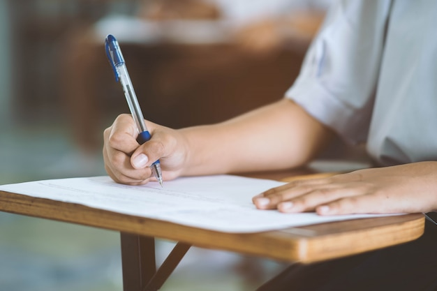Close up hand of student reading and writing exam with stress in classroom. Premium Photo