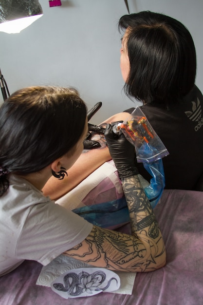 Close-up of the hand of a tattoo master in black gloves with a tattoo machine makes a tattoo according to the sketch Premium Photo