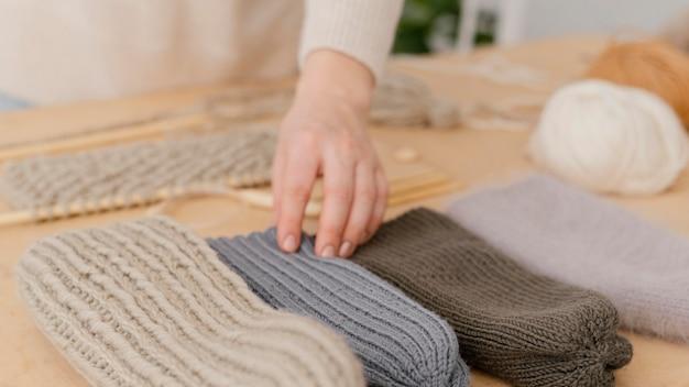 Cappelli lavorati a maglia toccanti della mano del primo piano Foto Gratuite
