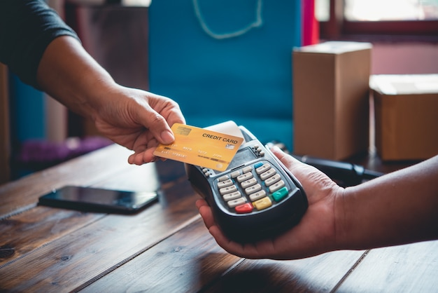 Close up of hand using credit card to pay by sending the credit card to the staff at the credit card