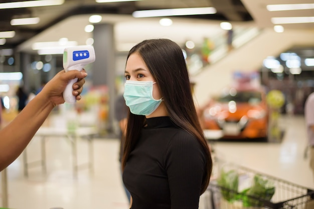 Close up hand using temperature gun with young woman , social distancing measure for covid-19 prevention in shopping center Premium Photo