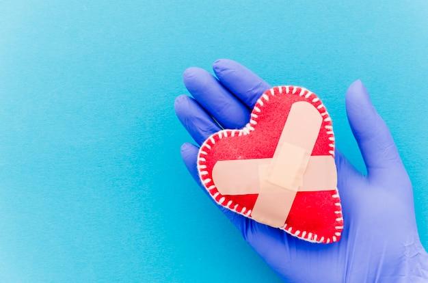 Il primo piano della mano che indossa i guanti chirurgici che tengono il cuore ha cucito il cuore del tessuto cucito con le fasciature attraversate sul contesto blu Foto Gratuite