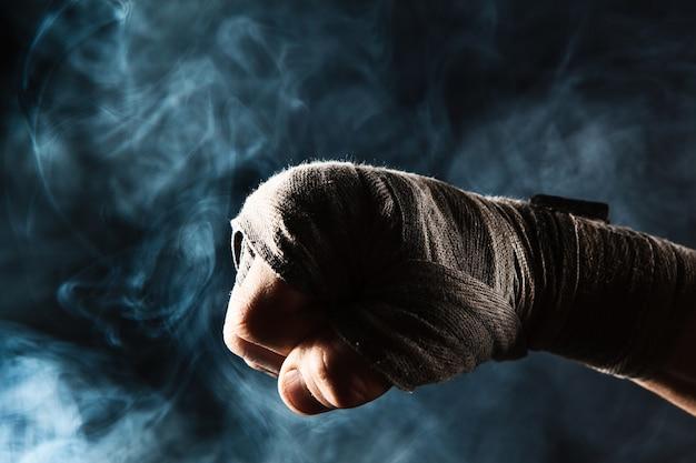 Mano del primo piano con la fasciatura del kickboxing di addestramento dell'uomo muscolare su fumo nero e blu Foto Gratuite