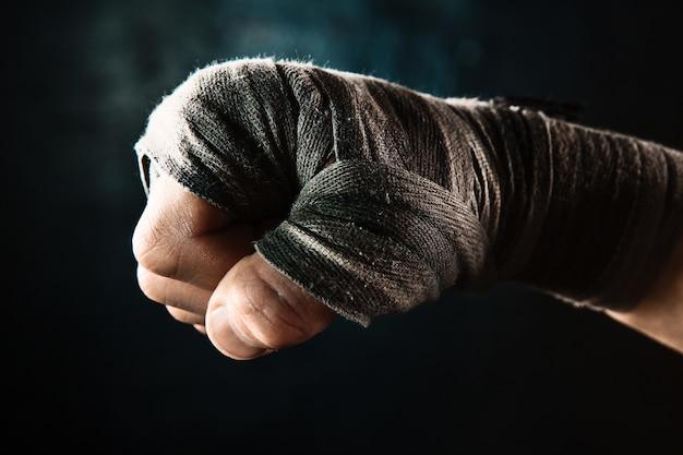 Close-up hand with bandage of muscular man training kickboxing  on black Free Photo