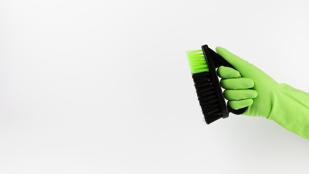 Close-up hand with green glove and black brush Free Photo