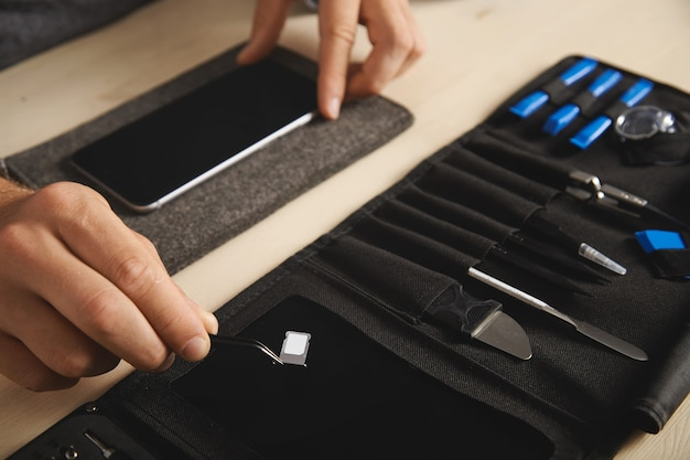 Close up on hand with pincher tool holding sim-card slot with nano sim above black magnet plate on portable tookit for electronic repeirment service Free Photo