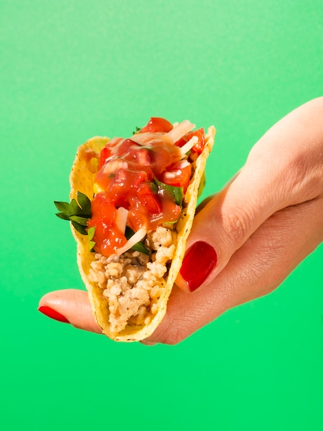 Close-up hand with taco and green background Free Photo