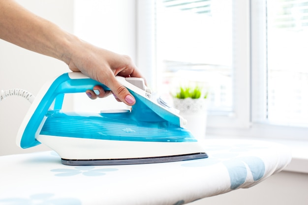 Close up hand of woman ironing clothes on the table Premium Photo