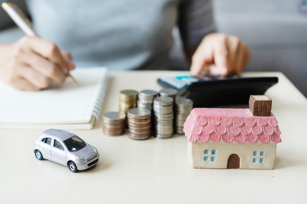 Close up hand writing while using calculator, stack of coins, toy house and car on table, saving for future, manage to success, finance concept. Premium Photo