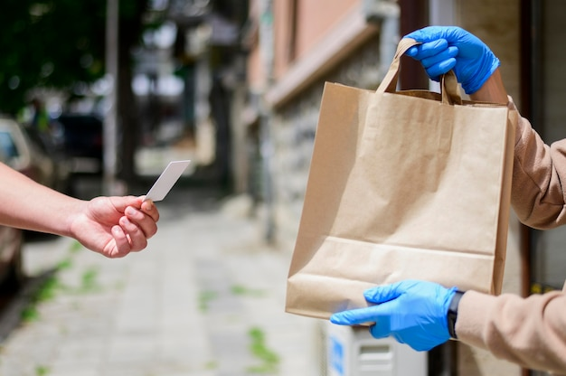 Close-up handing in paper bag to customer Free Photo