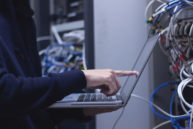 Close up of hands administrator  technician working on laptop in data center. Premium Photo