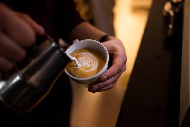 Close-up of hands barista making late art Premium Photo