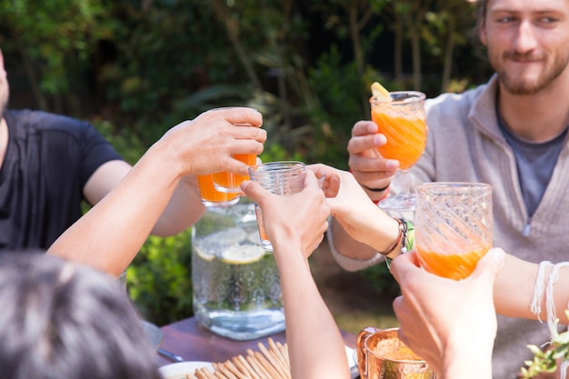 Close-up of hands clinking glasses with orange juice Free Photo