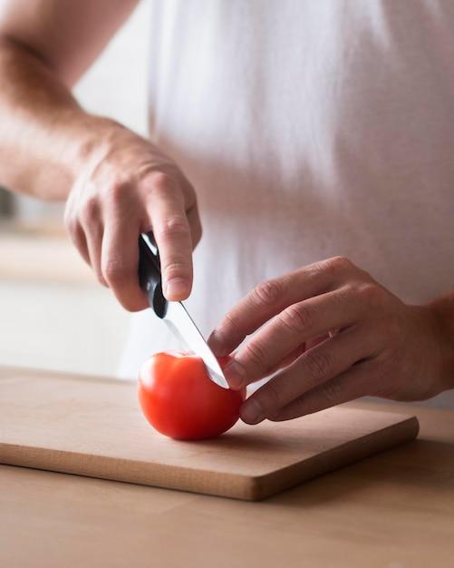 Close-up hands cutting tomato Free Photo