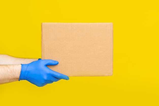 Close up hands delivery man medical gloves hold empty cardboard box on yellow background. service co