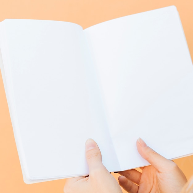 Close-up of hands holding blank white book against colored backdrop Free Photo