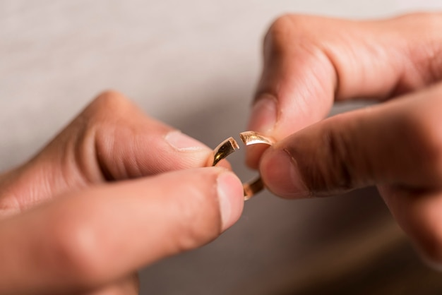 Close-up hands holding broken ring Free Photo