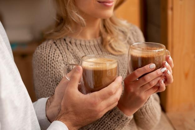Mani del primo piano che tengono le bevande calde Foto Gratuite