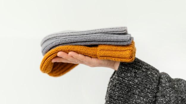 Mani del primo piano che tengono i cappelli lavorati a maglia Foto Gratuite