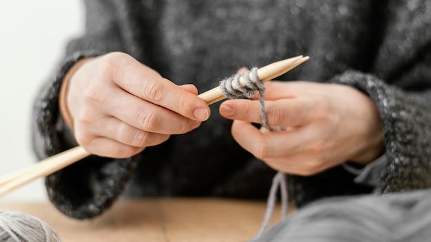 Mani del primo piano che tengono i ferri da maglia Foto Gratuite